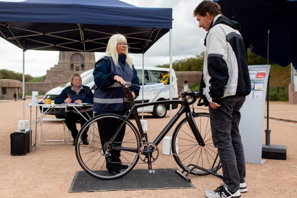 Eine Frau und ein Mann begutachten ein Fahrrad zur Registrierung.