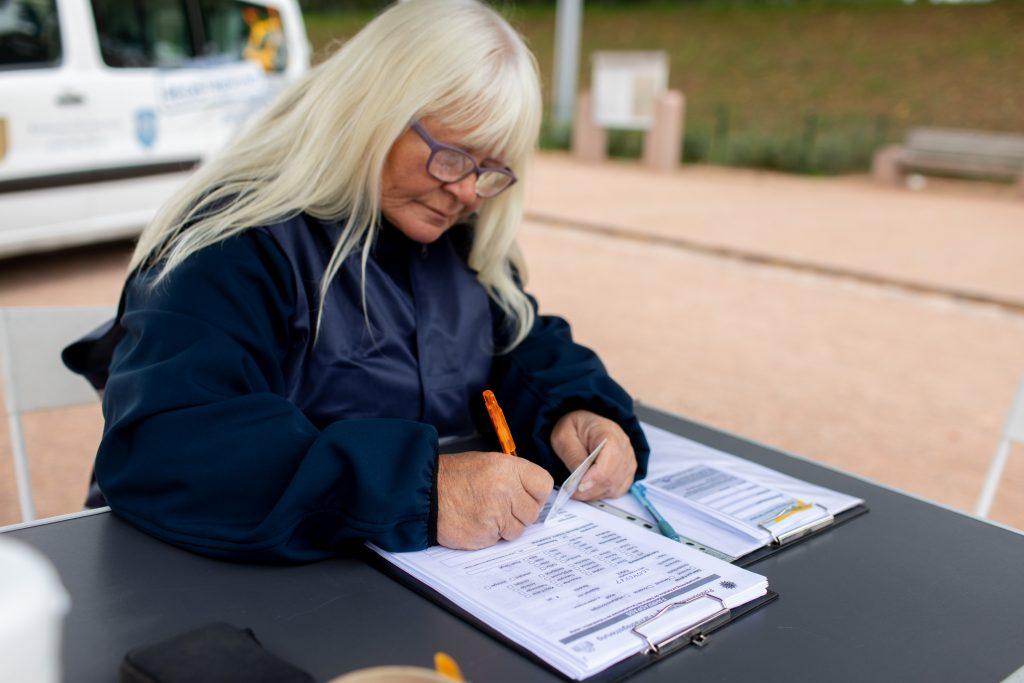 Eine Frau füllt ein Formular zur Fahrradregistrierung aus.