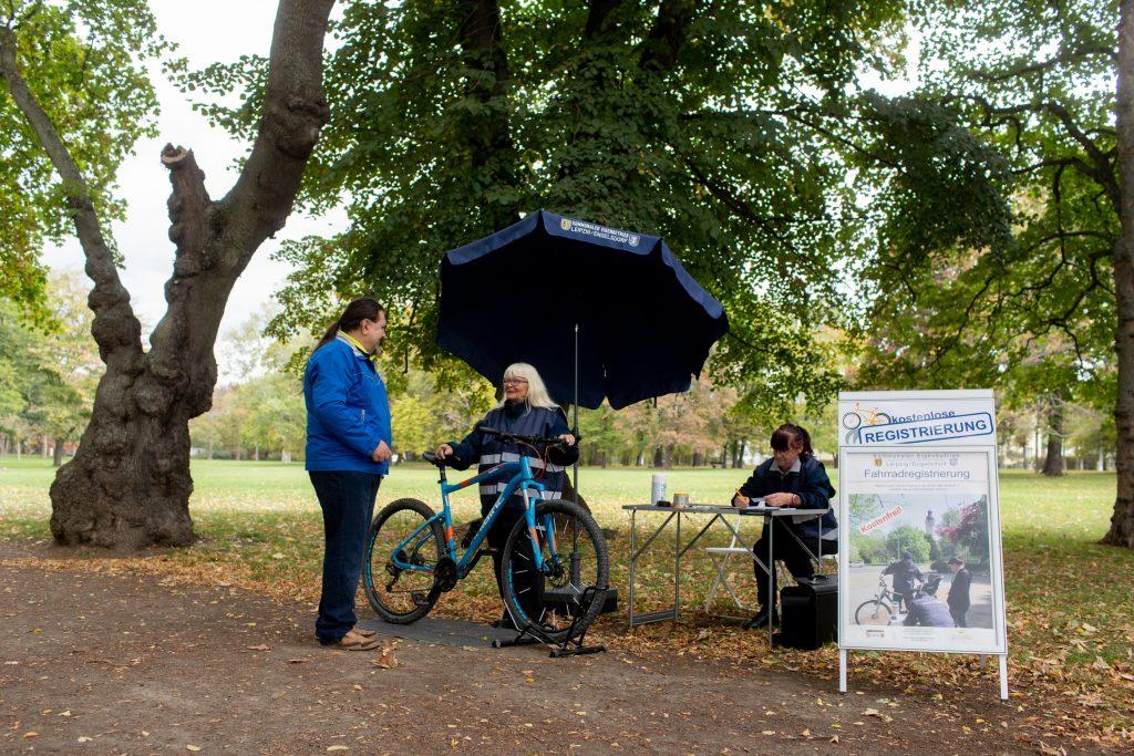 Drei Personen in einem Park registrieren ein Fahrrad.