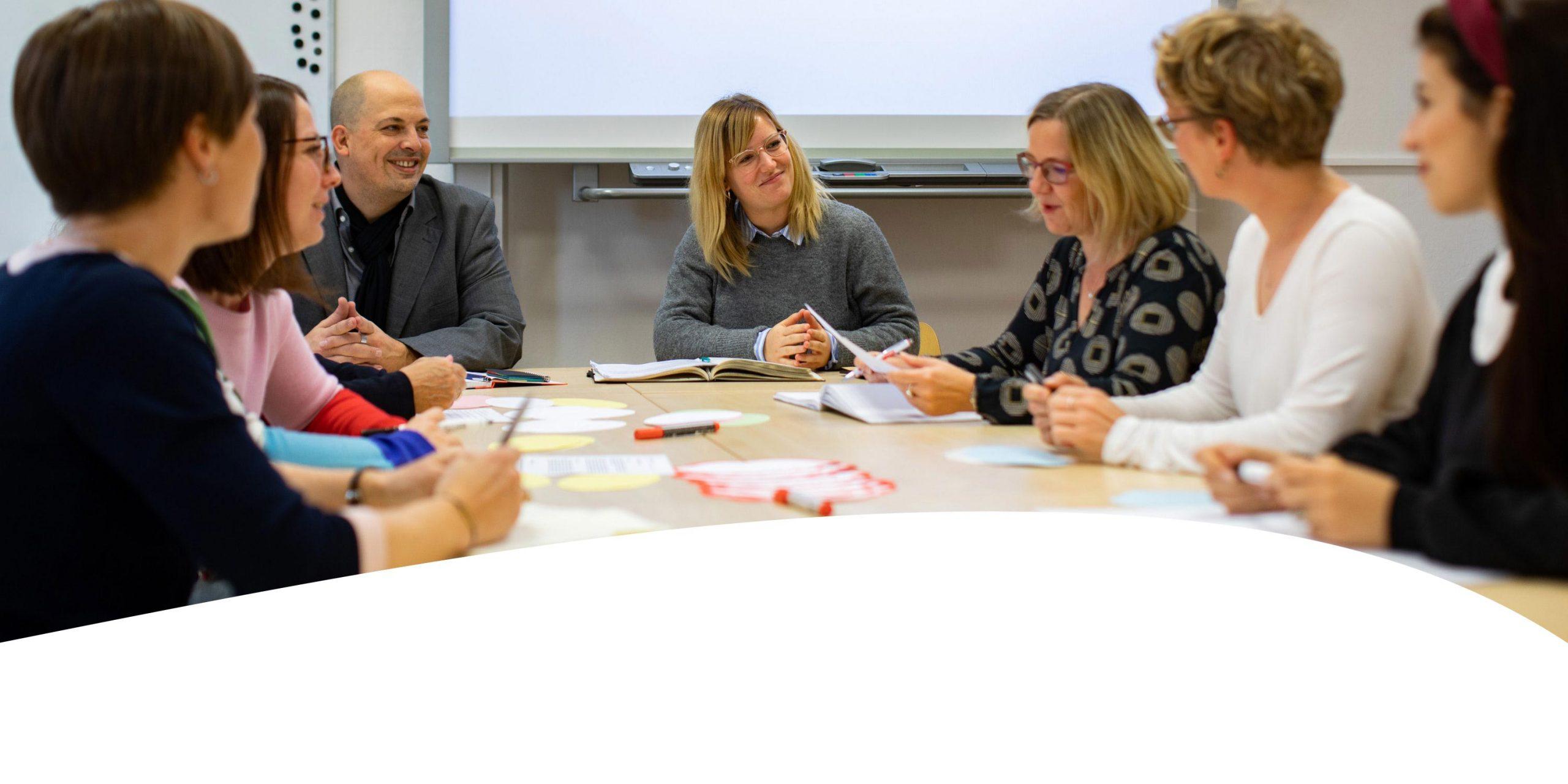 Mitarbeiterinnen und Mitarbeiter des KEE sitzen zu einer Beratungsrunde an einem großen Tisch..