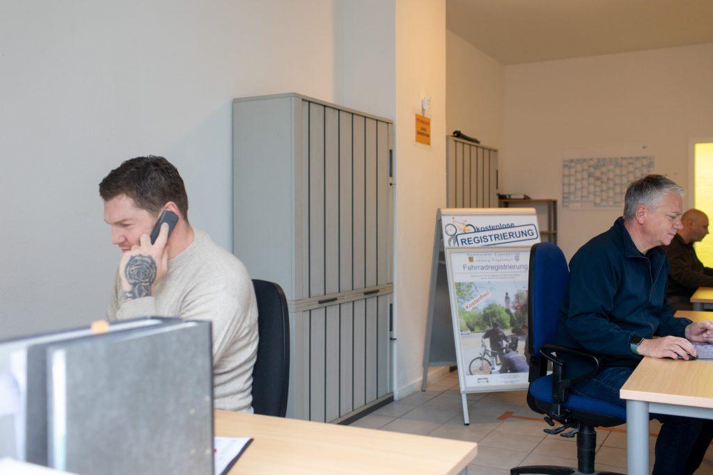 Drei Koordinatoren der Projekte des KEE arbeiten an ihren Schreibtischen.