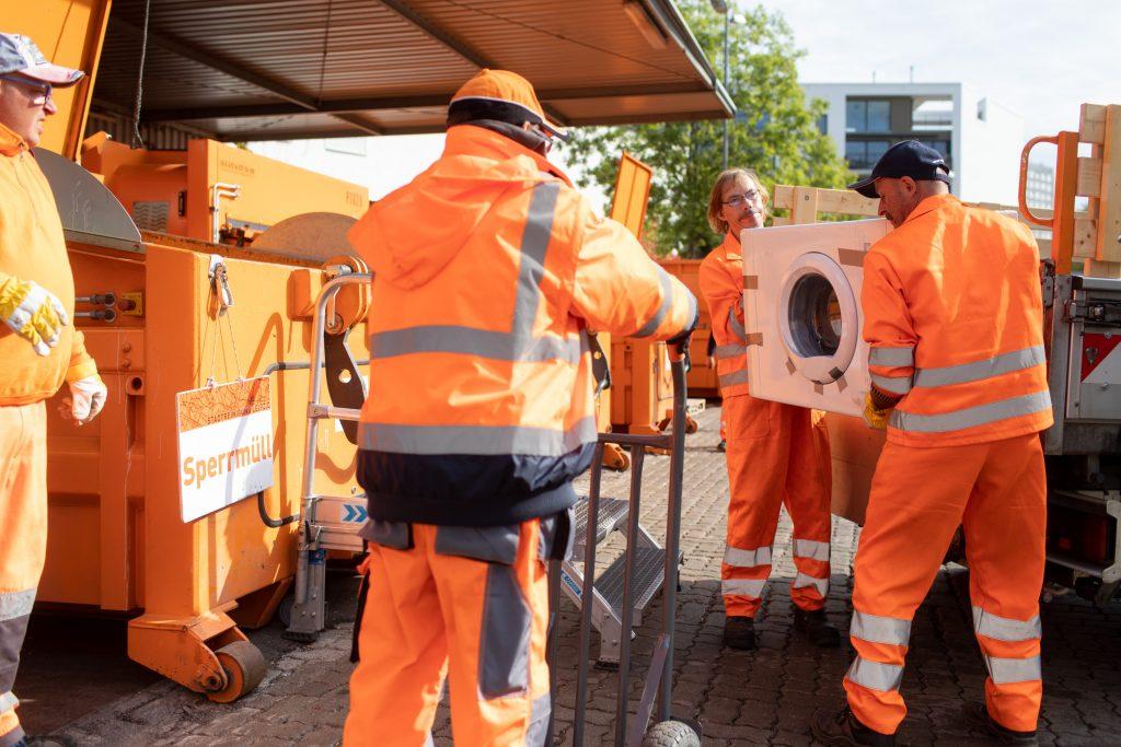 Vier Männer in orangefarbener Arbeitskleidung entsorgen eine Waschmaschine.