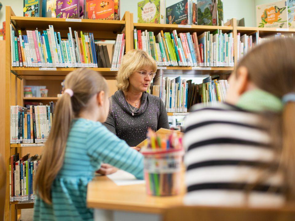 Eine Frau in einer Bibliothek liest zwei Mädchen aus einem Buch vor.