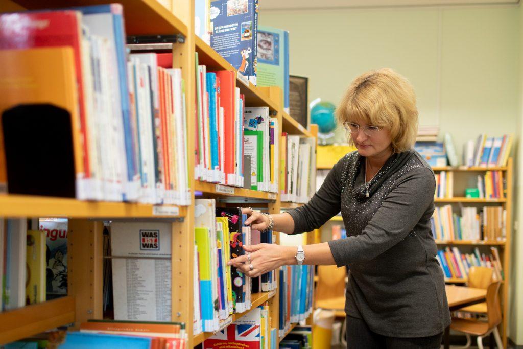 Eine Frau sucht ein Buch in einem Bücherregal in einer Bibliothek.