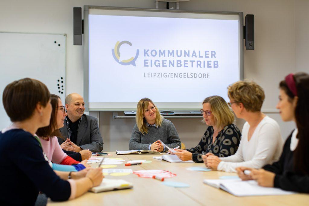 Mitarbeiterinnen und Mitarbeiter des KEE an einem großen Tisch zum Beratungsgespräch. Im Hintergrund das Firmenlogo.