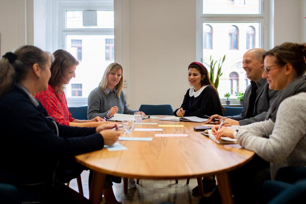 Mehrere Mitarbeiterinnen und Mitarbeiter des KEE sitzen an einem ovalen Tisch.