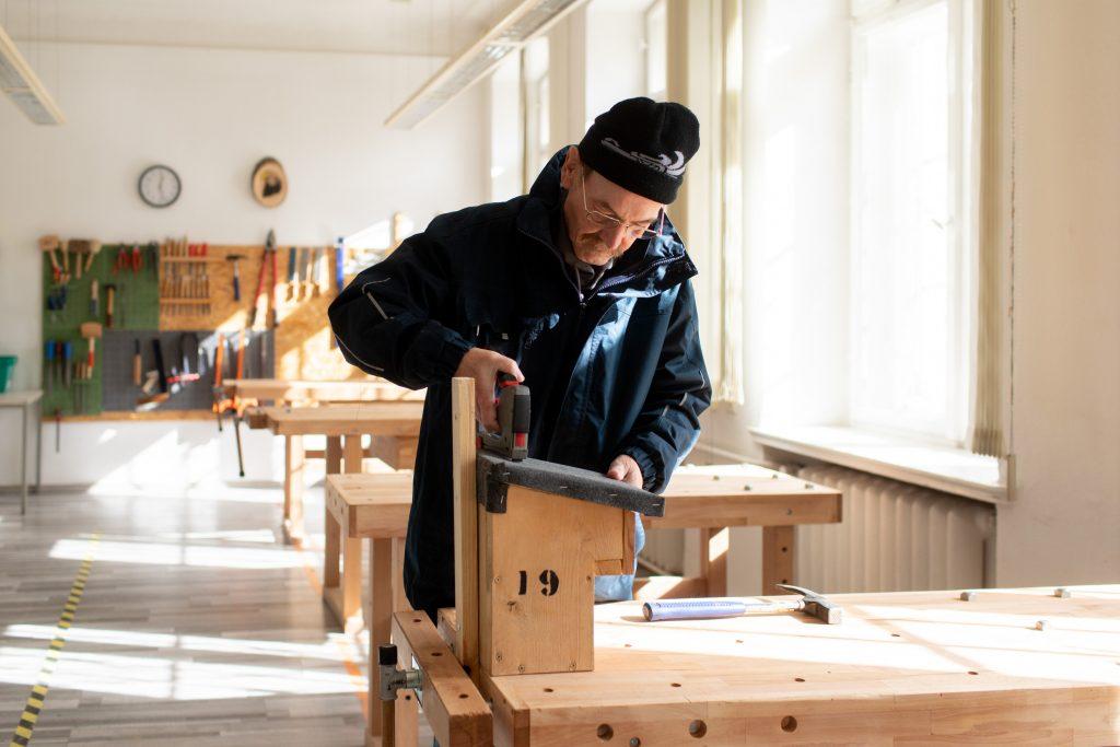 Ein Mann bearbeitet einen Nistkasten für Vögel aus Holz.