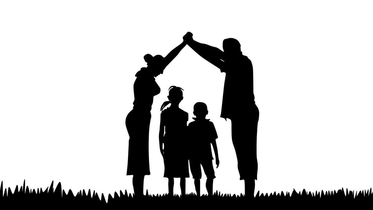 Silhouette einer Familie. Mann und Frau bilden mit ihren Armen ein Dach über zwei Kindern.