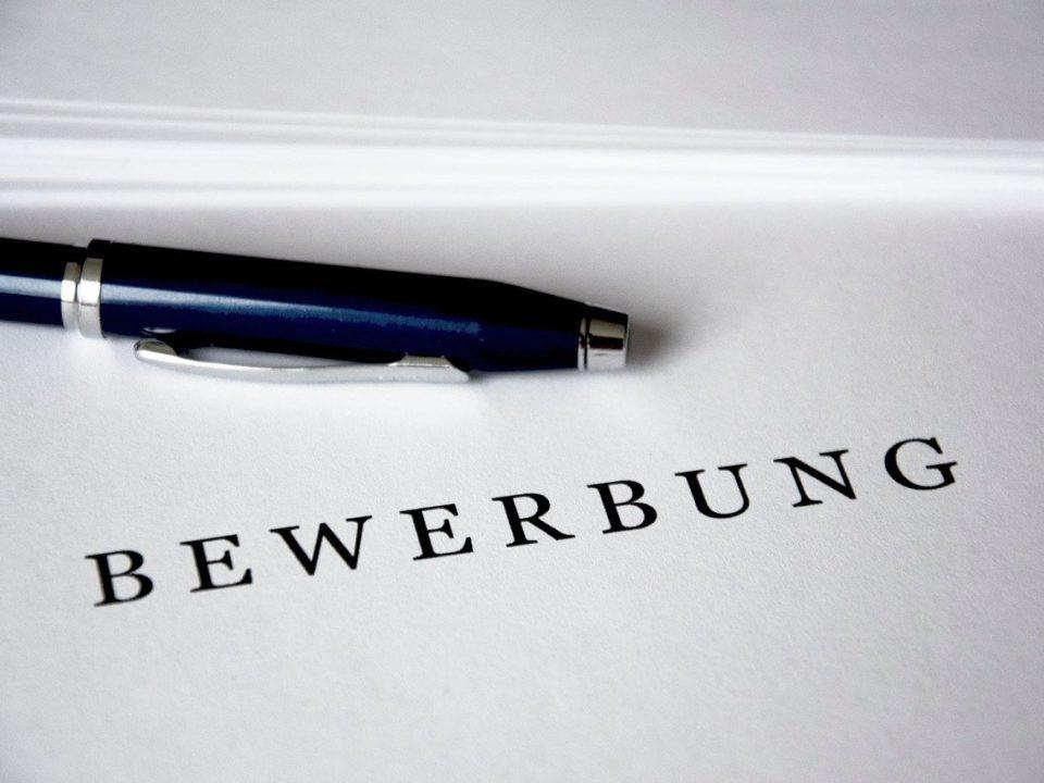 Ein Stift liegt auf weißem Papier. Darauf steht der Schriftzug Bewerbung.