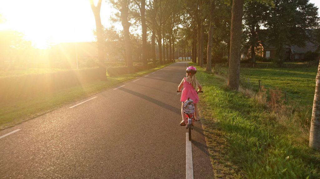Ein kleines Mädchen in einem rosa Kleid und mit rosa Fahrradhelm fährt auf einer Allee mit dem Fahrrad.
