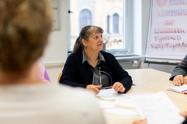 Eine Mitarbeiterin des KEE sitzt in einer Beratung an einem Tisch.